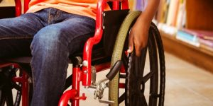 Closeup photo of wheelchair with red frame and black hand on large wheel.