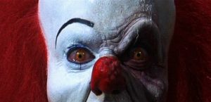 Close up of white-faced, red-nosed clown without facial symmetry.