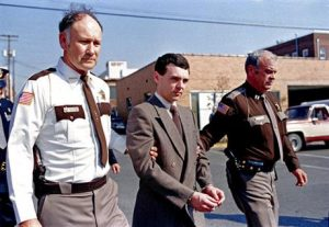 Angel of Death serial killer Harvey. MS of handcuffed man with 2 guards.