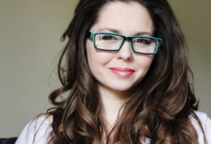 Headshot of brunette Amber Rose Carlson in glasses, who addresses rape & male privilege.