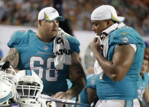 Two linemen in Dolphin turquoise jersies w/o helmets talk to one another off field