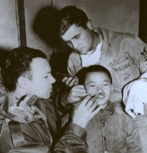 Blsck n white photo of Dr. Millard (left) examining Asian cleft lip patient.
