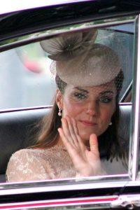 Plastic surgery ideal: Duchess of Cambridge with hat on waving from a car.