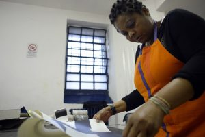 Afro-Italian inmate in orange apron working at table.