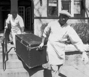 Black trunk of privileged killer Einhorn. Trunk with body being carried by two men.