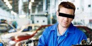 Car repair fraud. Mechanic in blue coveralls.