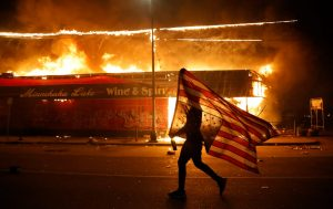 An upside down flag, a sign of distress, next to a burning building on Thursday, May 28, 2020, in Minneapolis. AP /Cortez